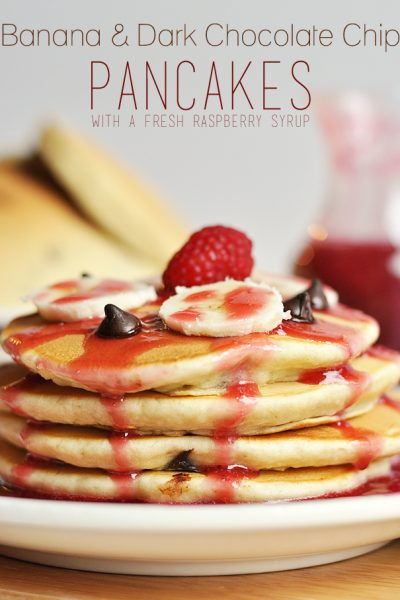 Enjoy this delicious and beautiful Banana and Dark Chocolate Chip Pancakes Recipe for a special occasion, or just because! Topped off with a Fresh Raspberry Syrup