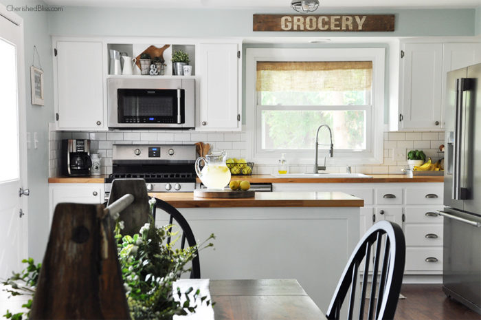 This industrial farmhouse kitchen is both functional and inviting. Stainless steel appliances bring a professional industrial look while adding softer elements provides the comfort of a farmhouse.