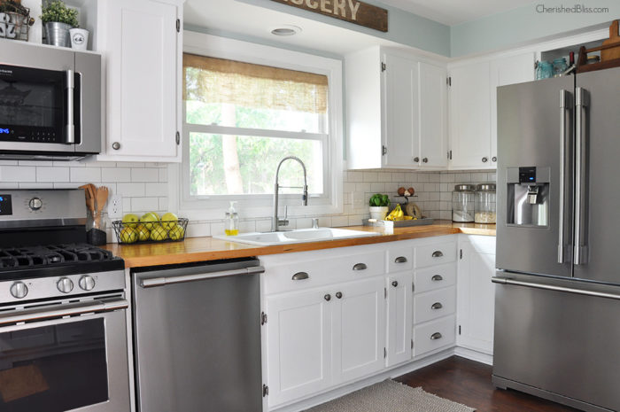 This industrial farmhouse kitchen is both functional and inviting. Stainless steel appliances bring a professional industrial look while adding softer elements offers the comfort of a farmhouse.