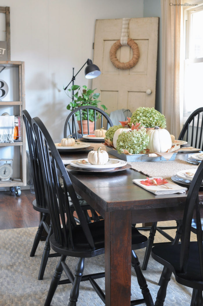 A simple Farmhouse Fall Tablescape with a hydrangea and pumpkin centerpiece, burlap table runner, and fall leaves to accent the simple place settings.