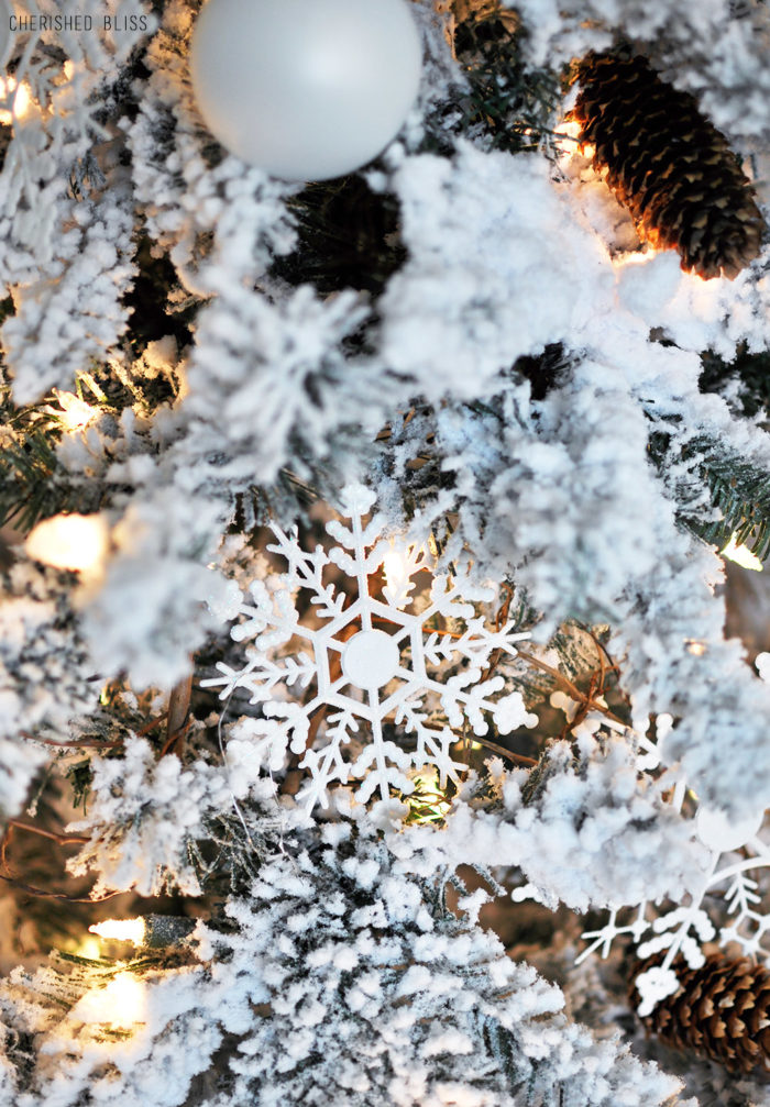 A simple White Flocked Christmas tree with white ornaments and a few rustic touches