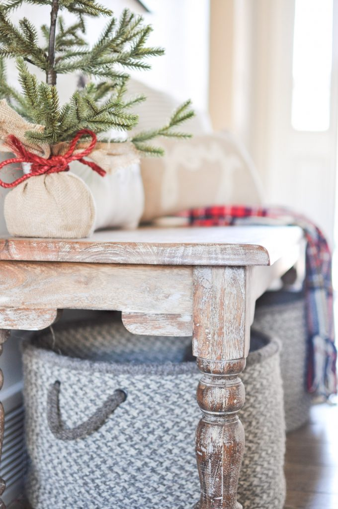 Take a tour through a simple farmhouse style Christmas Entryway. A basic bench, throw pillows, and a blanket create this cozy entrance!