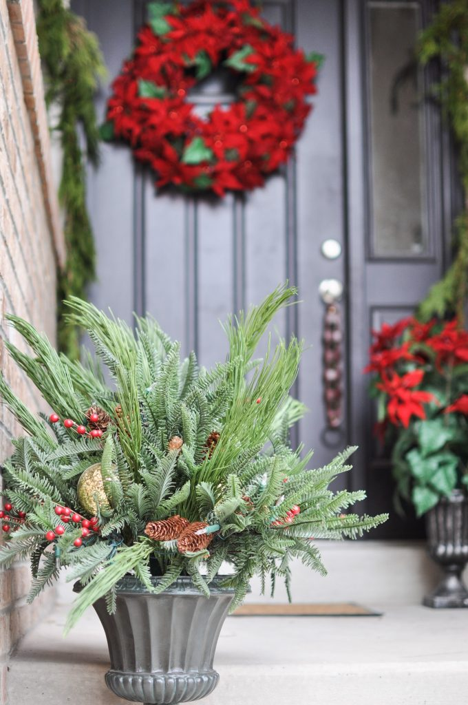 Looking for simple Porch Decorating Ideas? Create a classic appeal with these traditional poinsettias and cedar garland for a Classic Christmas Porch.