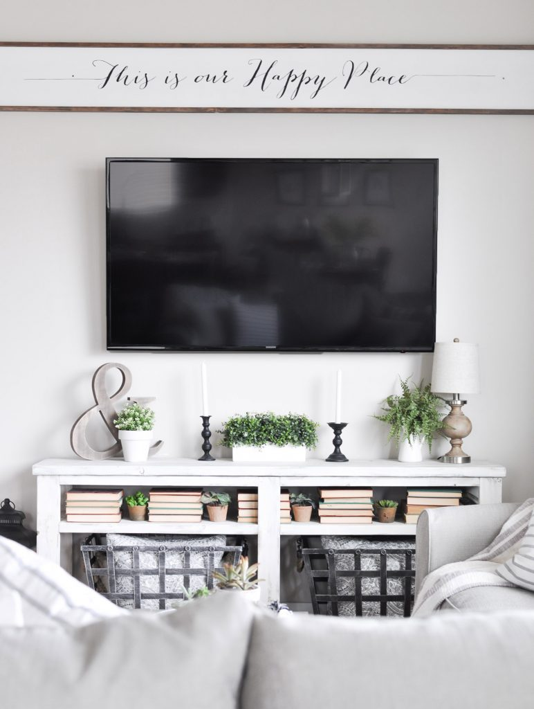 This Simple Summer Mantel is decorated using simple whites and greens to celebrate the growth of the season mixed with a few wood tones for coziness!