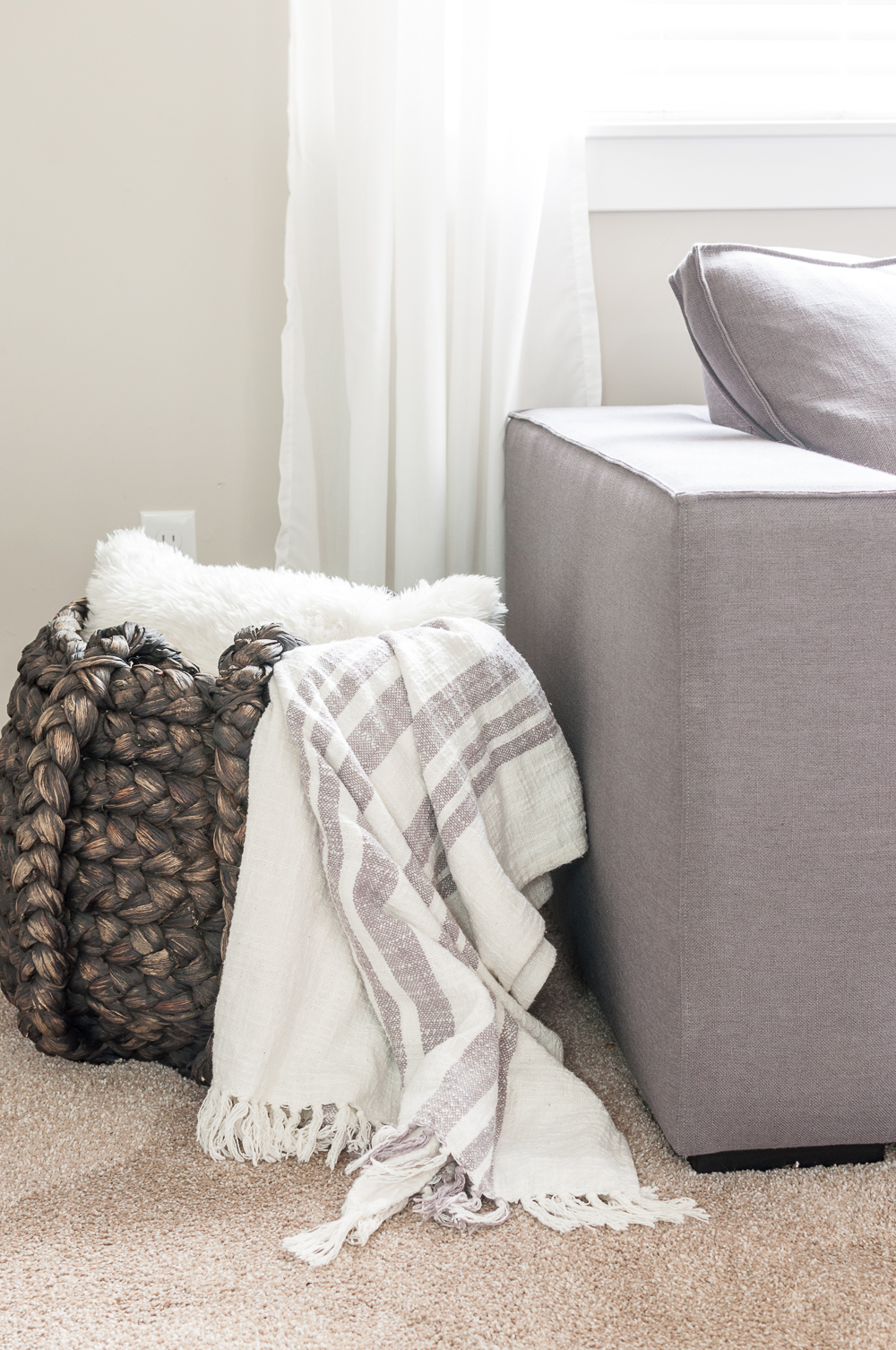 bring in warm textures to a minimalist living room to provide a cozy element that feels like home.