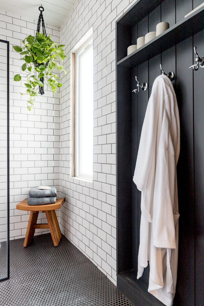 Industrial bathroom featuring white subway tile, black vertical shiplap and black hexagon flooring.