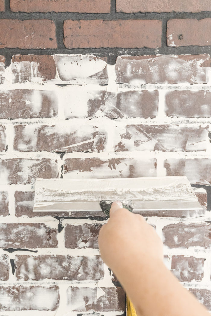 Add sheetrock compound to faux brick wall panels to give it a realistic appearance.