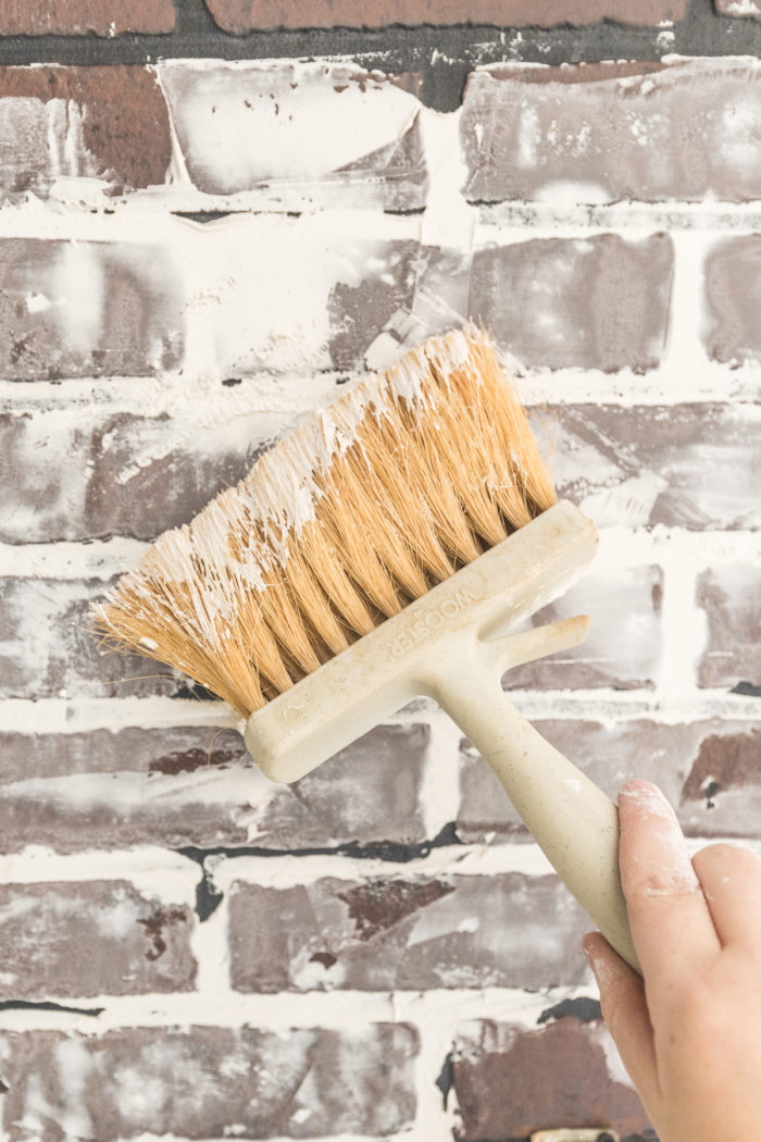 Use a masonry paint brush to add texture to the sheetrock compound on a faux brick wall.