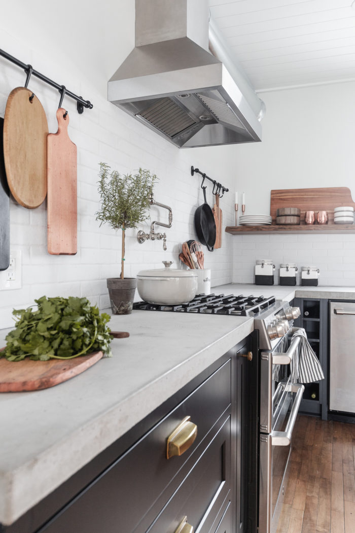 Concrete countertops in a kitchen with stainless steel appliances.