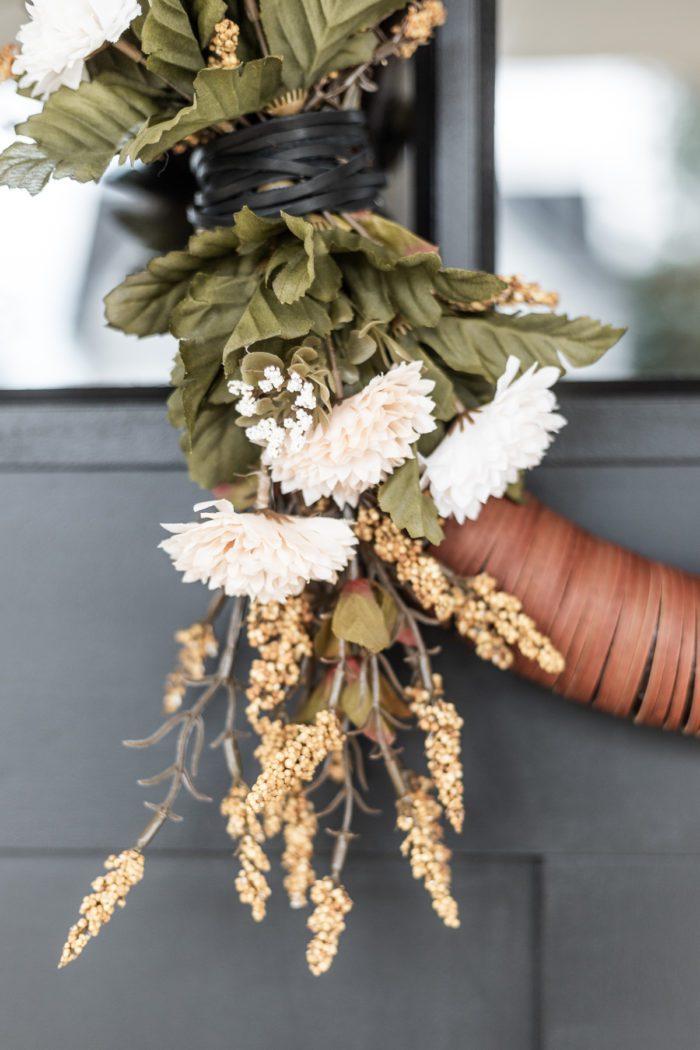 Wrap Black leather around florals on wreath.