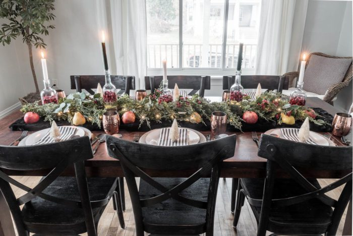 Christmas Table decor with tall glass bottles used as vases.