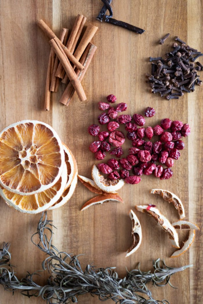 Dried Fruits and seasonings to make stovetop potpourri. Ingredients include dried oranges, dried cranberries, cinnamon sticks, whole cloves, and rosemary.