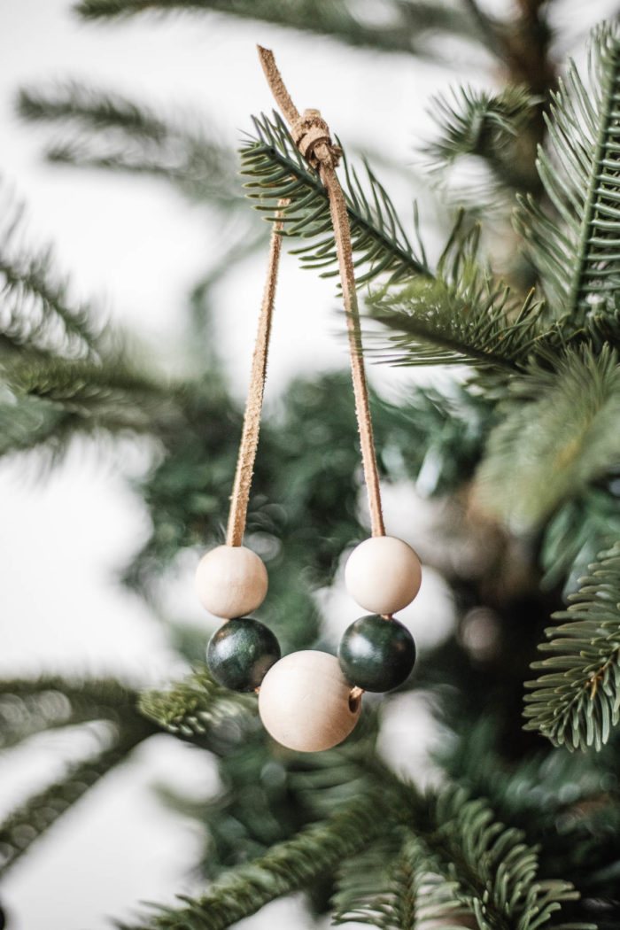 Wooden Bead Christmas Ornament with leather lacing hanging on Christmas Tree.