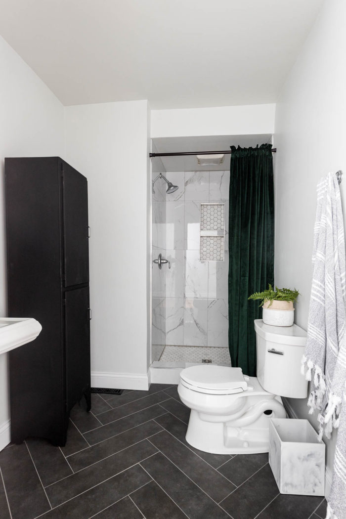 Small Bathroom renovation, stand up shower with marble tile and black herringbone floors.