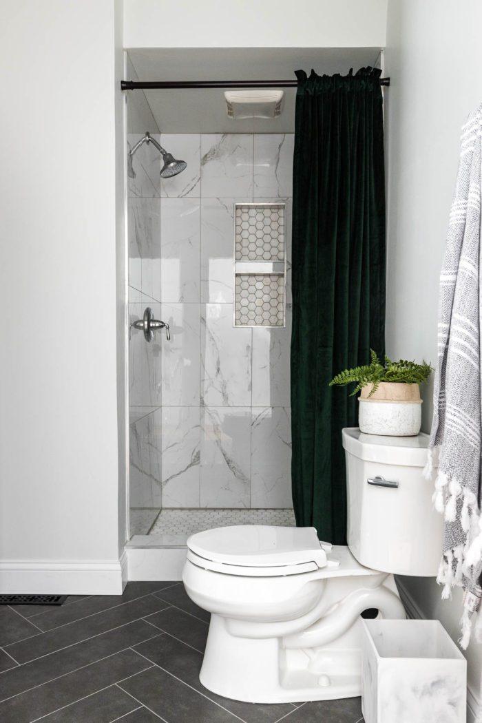 Marble tile in shower with green velvet shower curtain