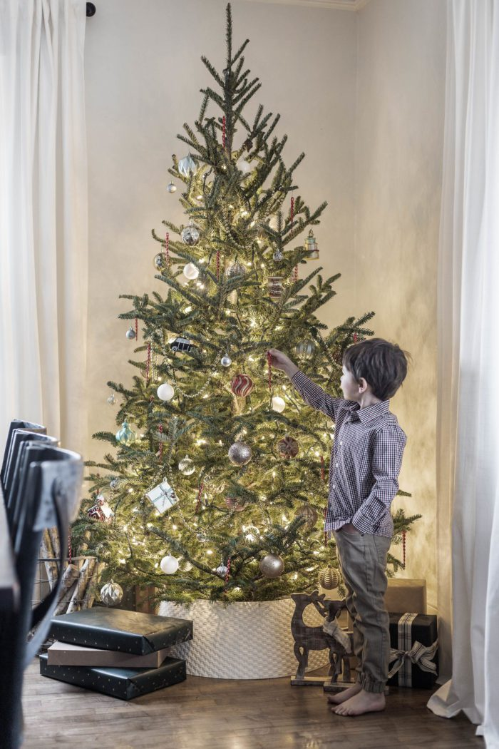 little boy decorating a nostalgic Christmas tree - the perfect holiday tradition.