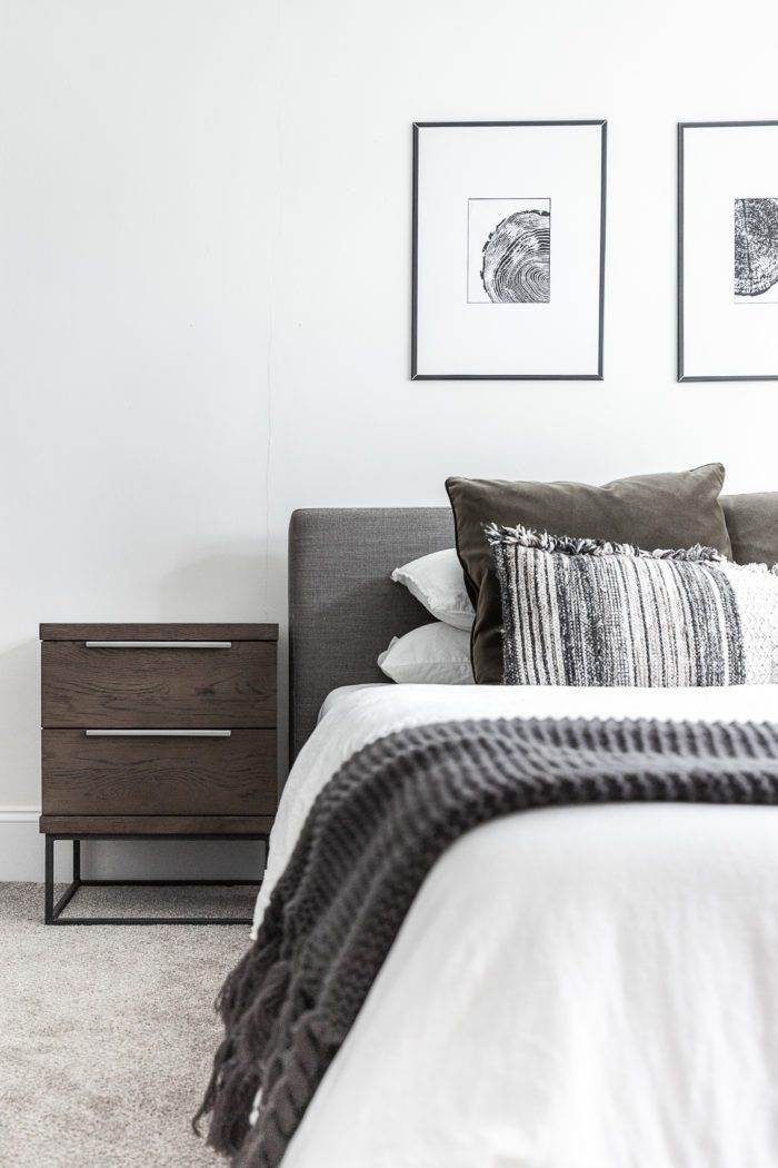Master bedroom with gray headboard, minimalist design, black and white art, and white bedding.