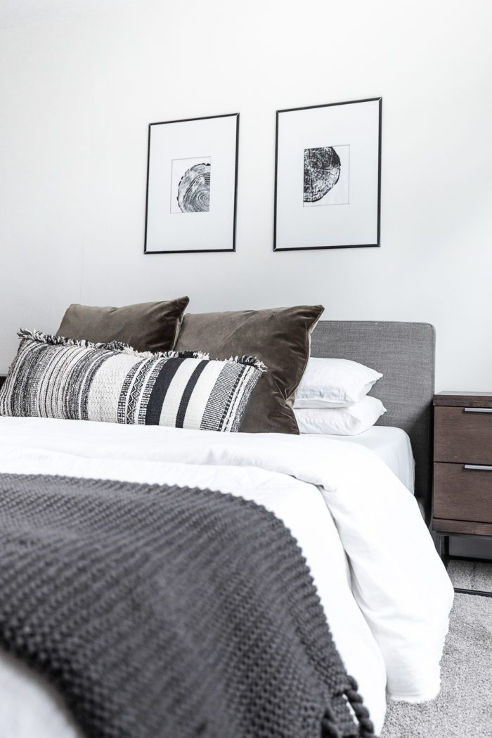Black and white tree ring art over cozy minimalist bed.