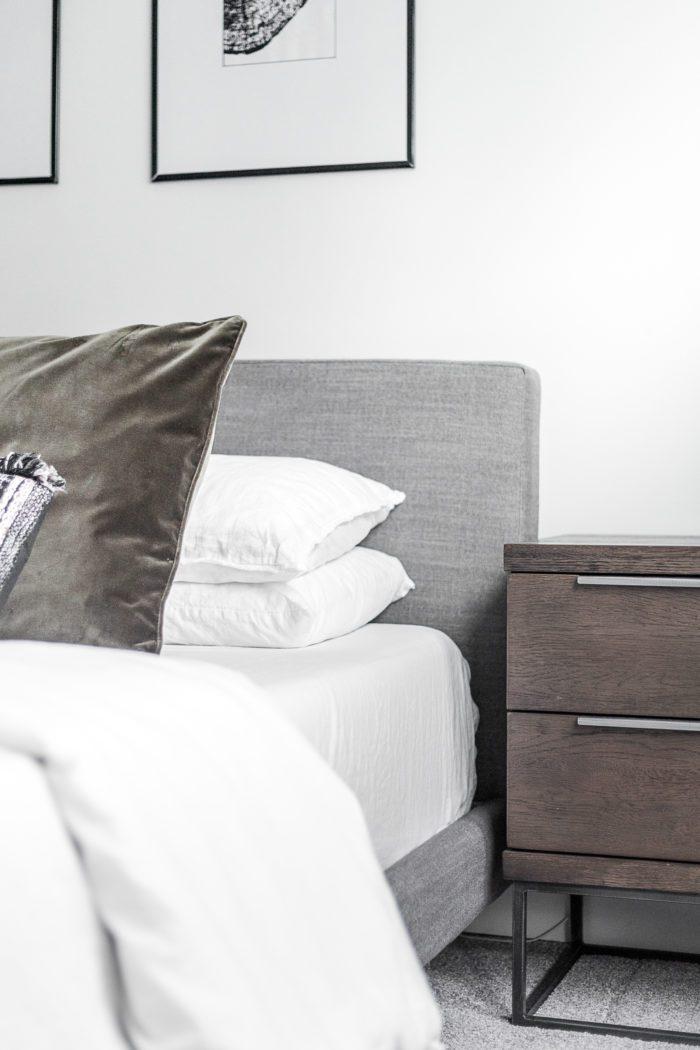 Gray upholstered headboard, velvet pillows and dark wood nightstand.