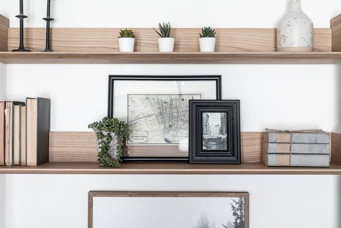 Desk Shelf Styling with black frames, books, and faux greenery.