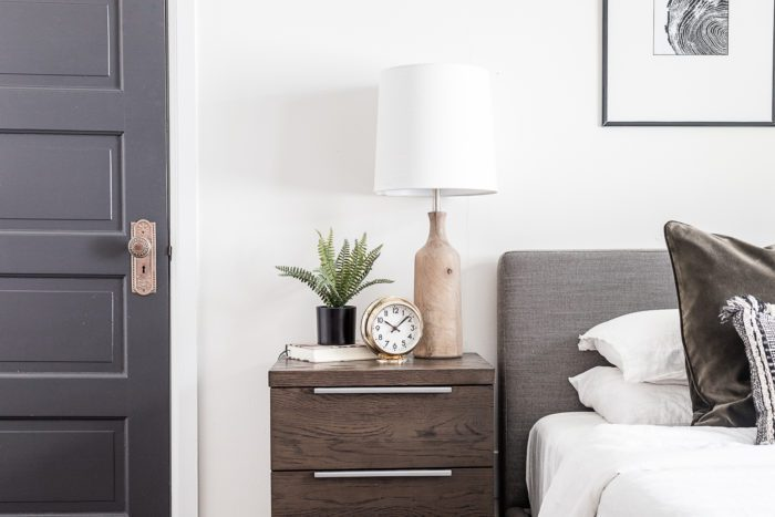 Dark wood nightstand next to upholstered headboard and black interior doors.