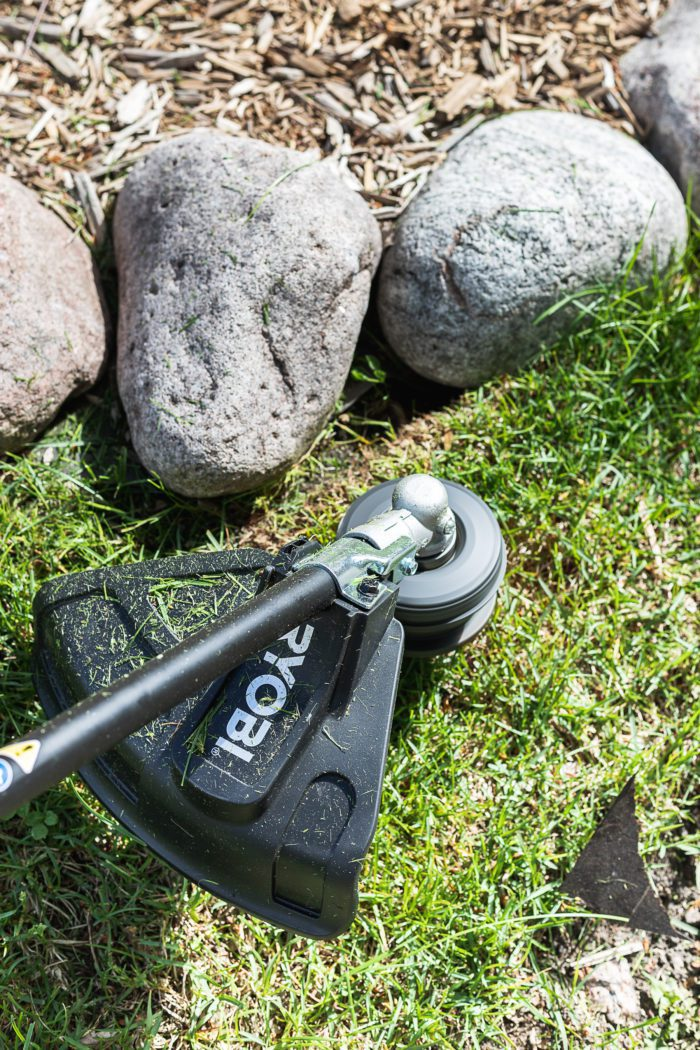 battery operated trimmer being used around landscaping rocks.