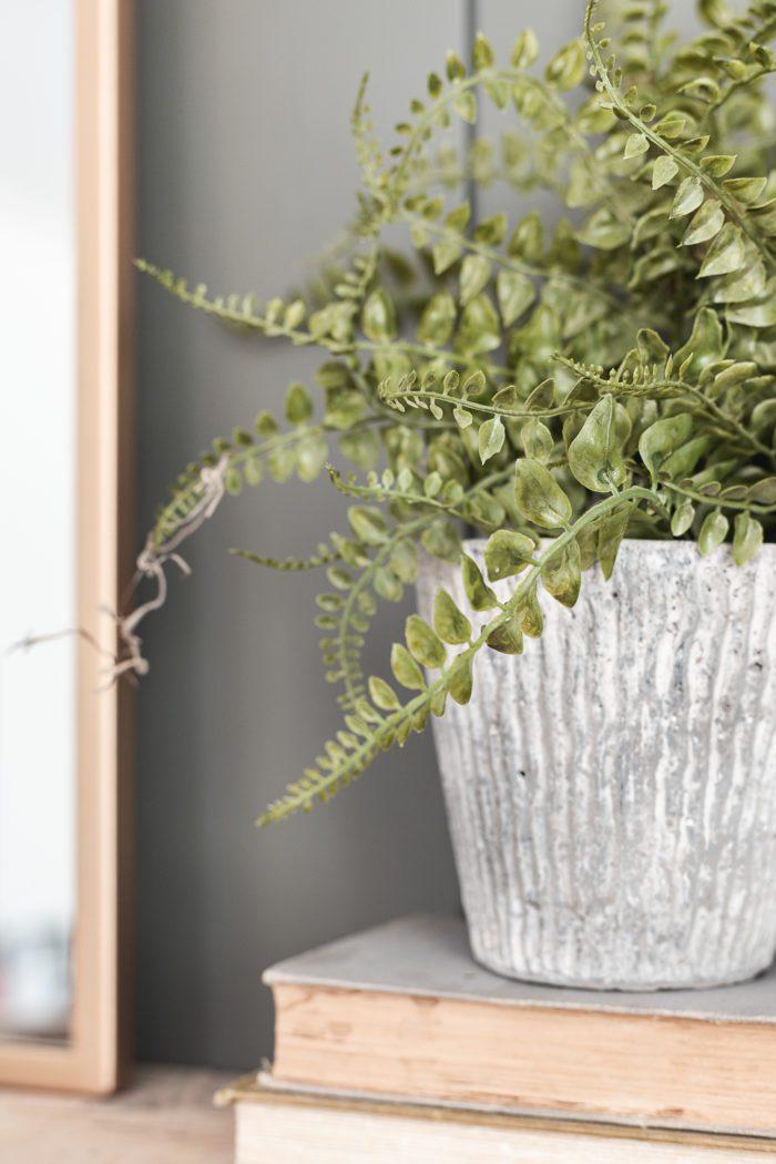 faux fern in a concrete pot for summer mantel decor.