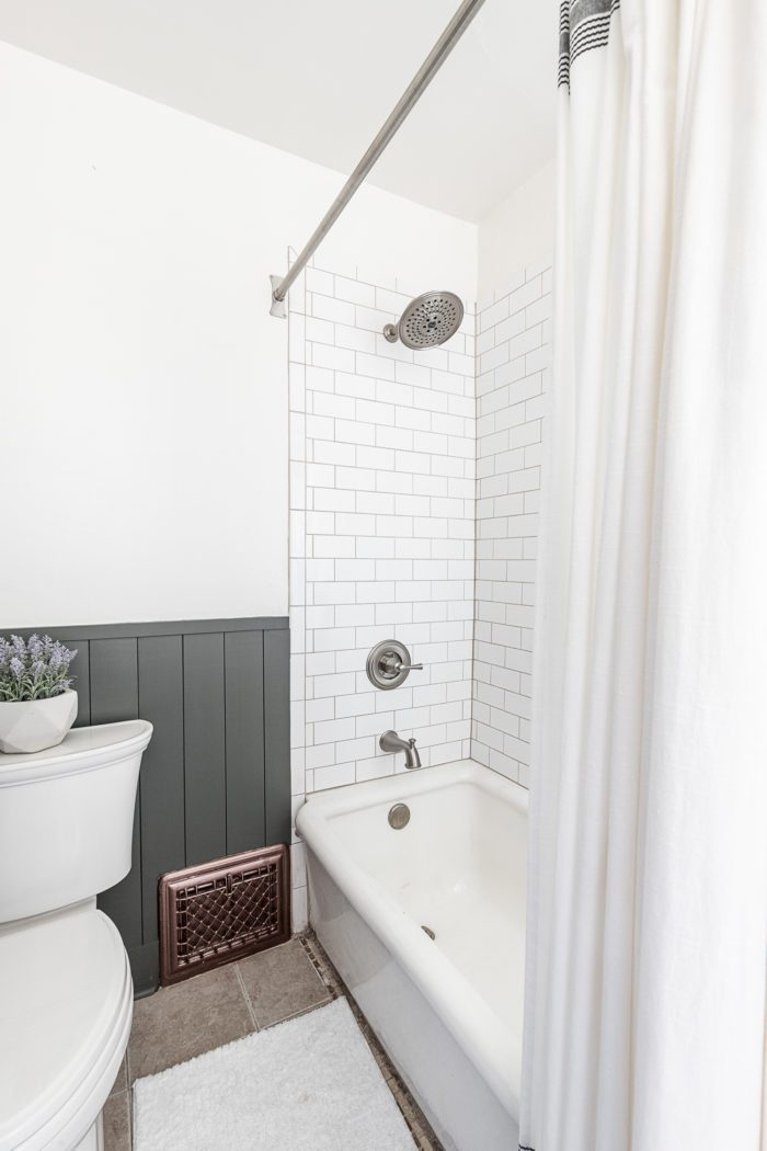 Boys Bathroom with dark green vertical shiplap and subway tile in shower