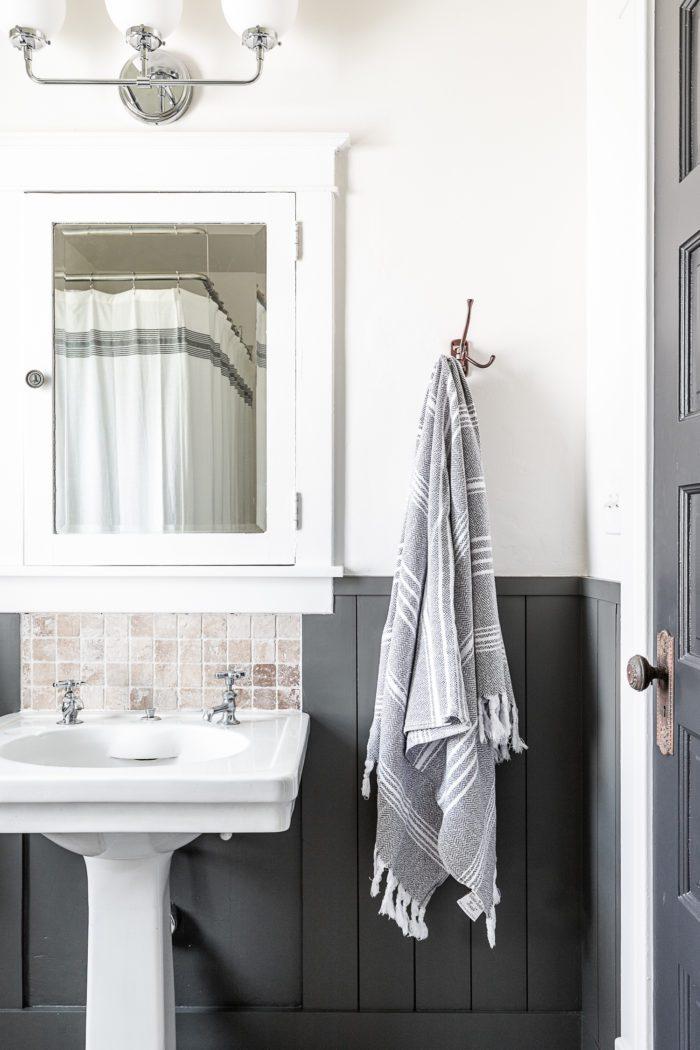 Boys Bathroom with pedestal sink and swinging hooks.