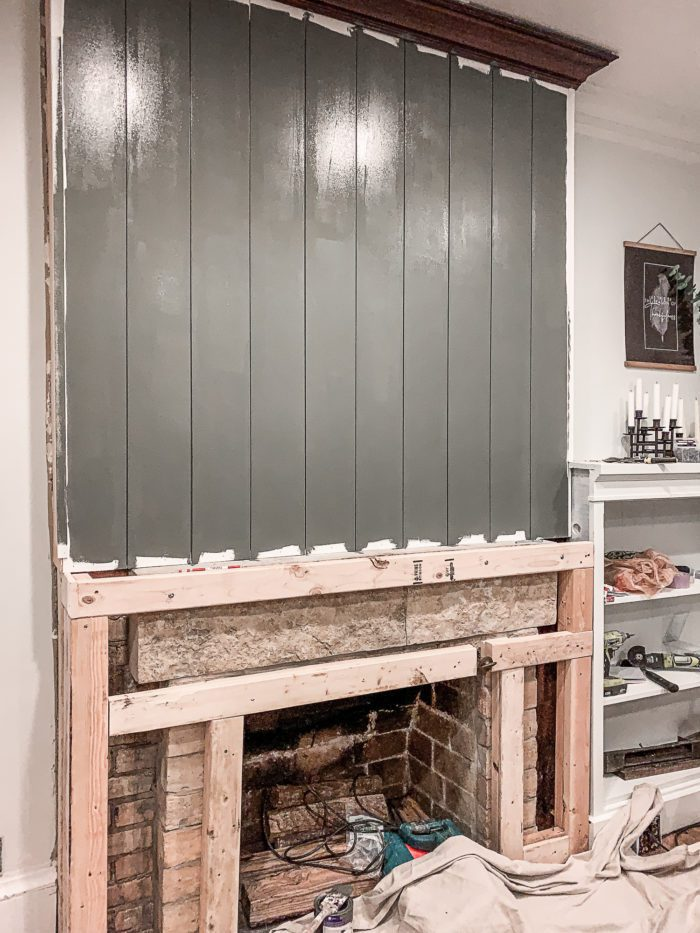 Painted vertical shiplap above fireplace