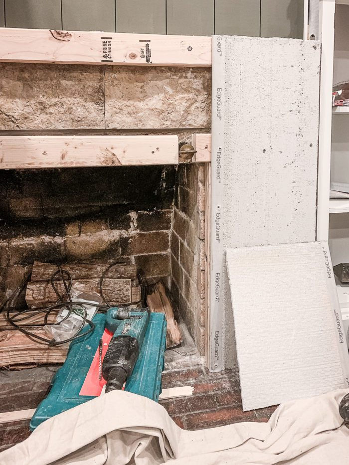installing cement board over fireplace to create cement fireplace look.