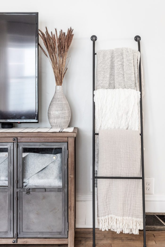 Blanket ladder next to tv stand with Fall Decor.