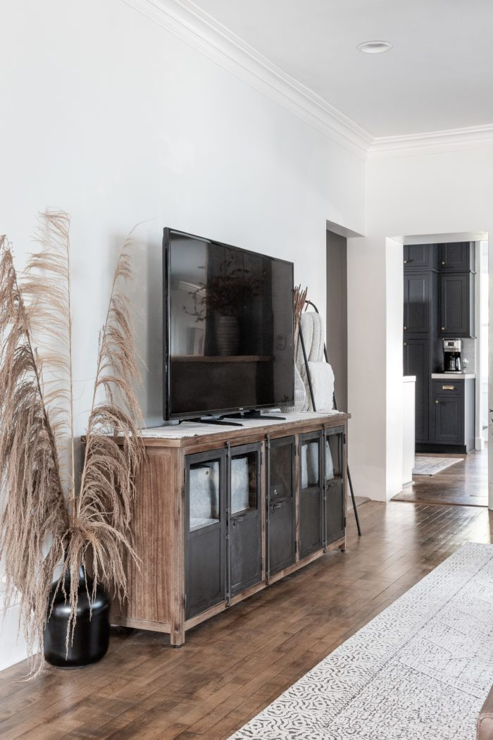 Media unit with tv and tall Uva Grass is black glass jug.