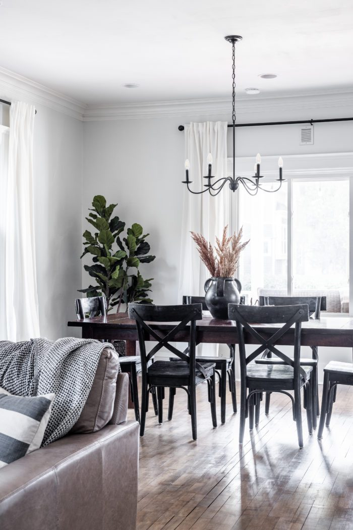 Neutral Fall Home Tour with ceramic jug on dining room table with black chairs.