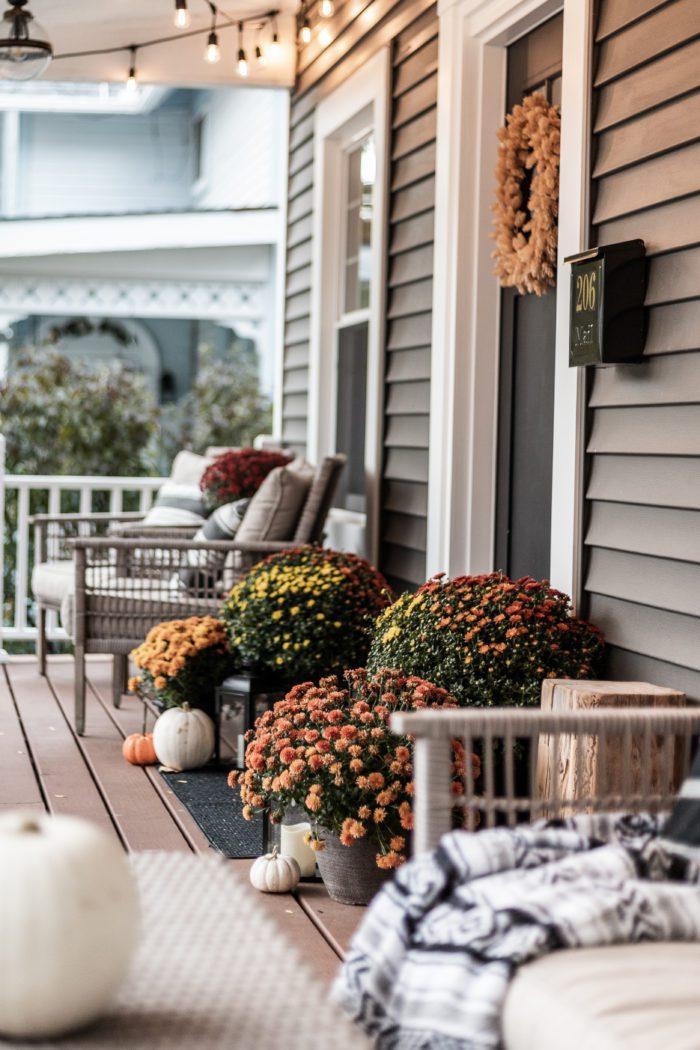 Mums, pumpkins, and lanterns around the front door.