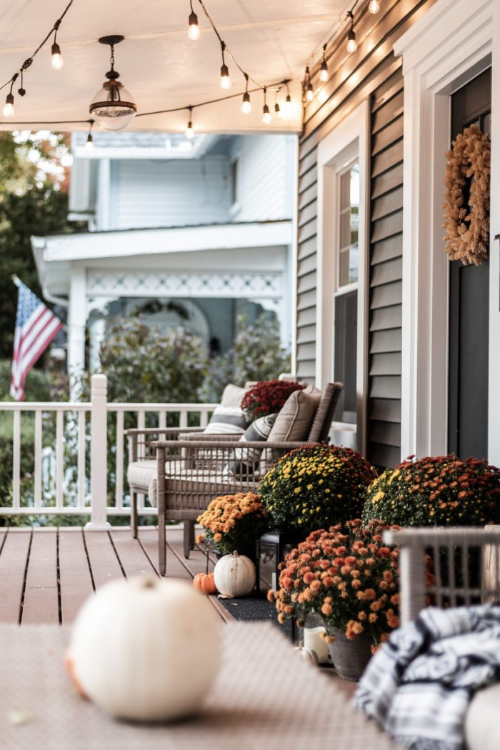 Fall front porch with pumps around the door and cafe lights hanging on the ceiling