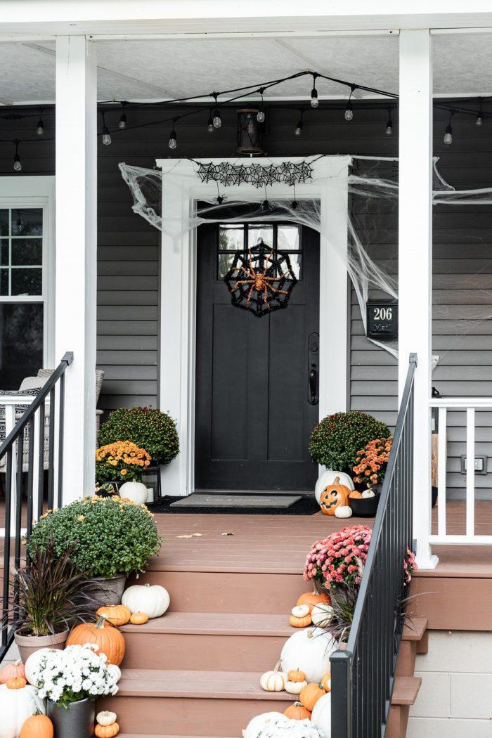 Black front door with halloween spider wreath and webs.