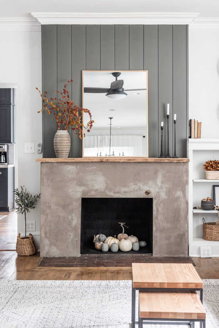 Concrete fireplace with vertical shiplap decorated for Fall.