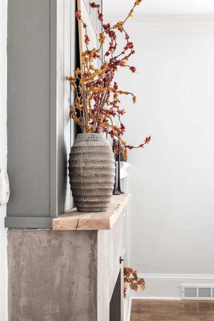 Faux Fall Stems in earthy vase on fireplace mantel.