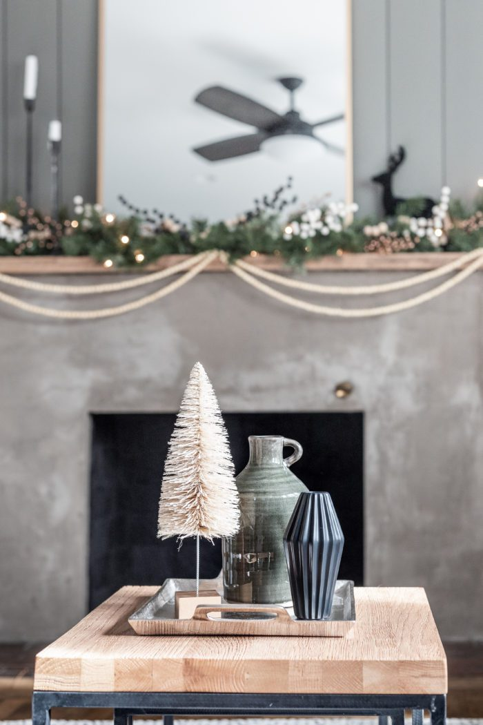 Winter Decor Items on Coffee Table in front of concrete fireplace.