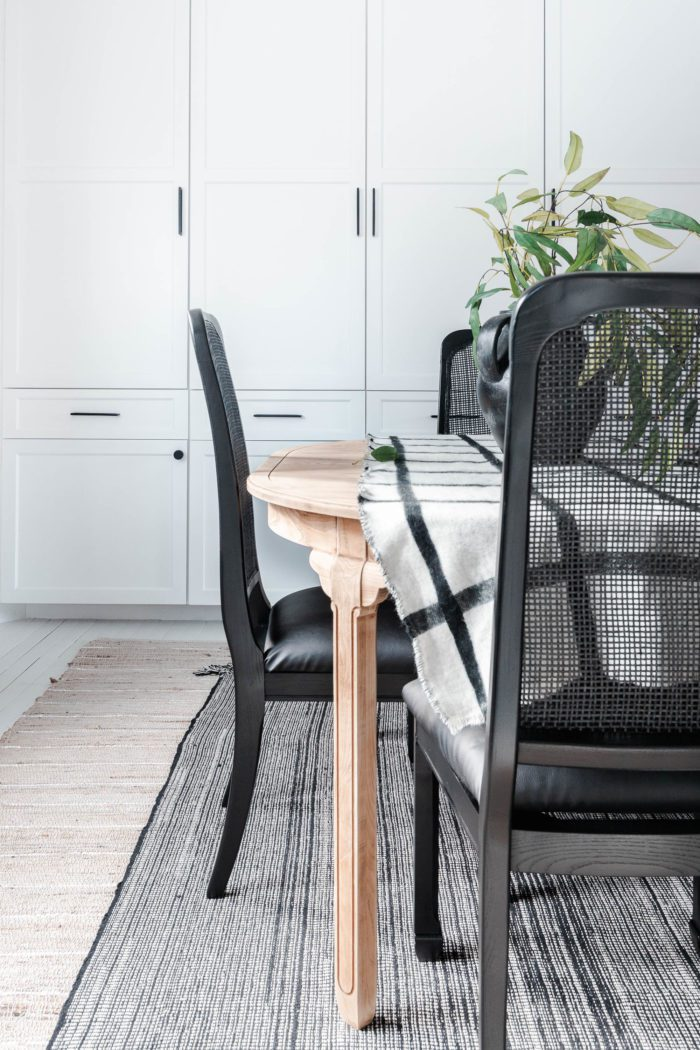 Raw wood table with black cane chairs in breakfast room with white cabinets.
