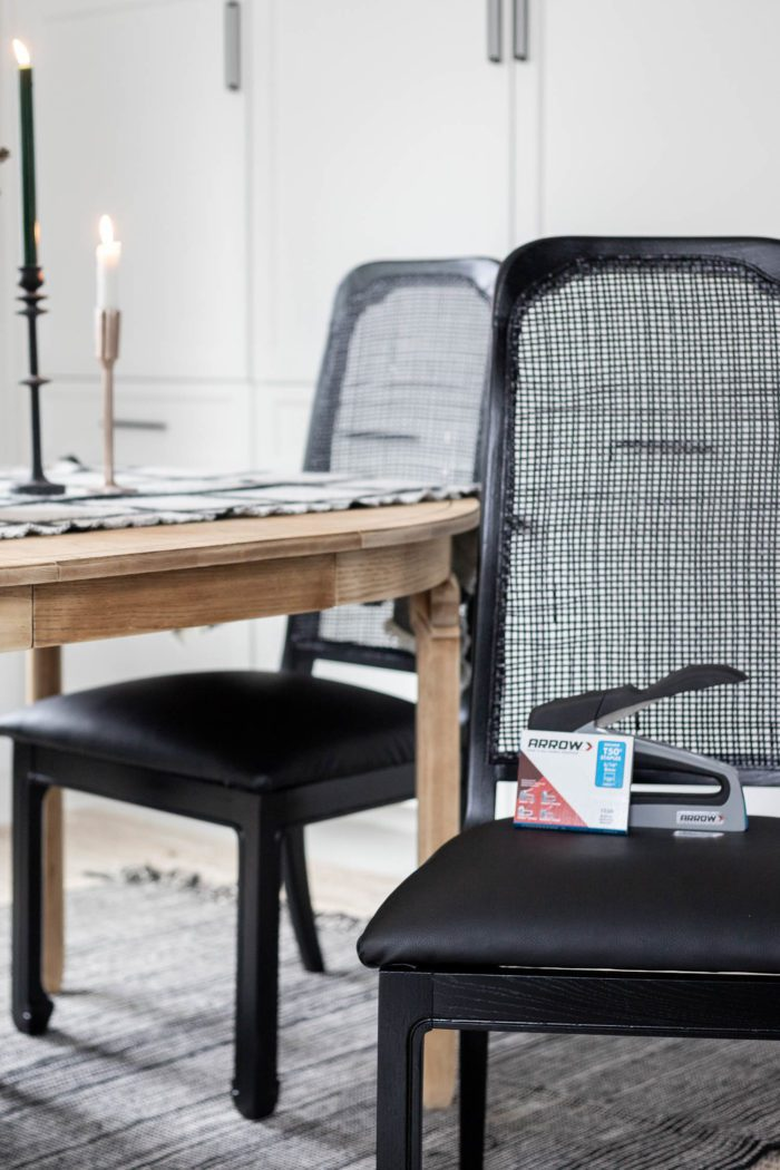 This old cane chair gets a modern makeover with black paint and a recovered seat cushion in faux black leather for a modern look.
