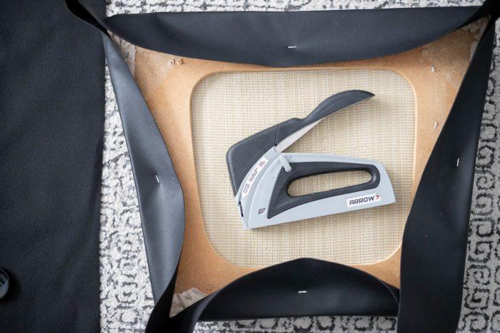 Begin stapling new fabric to chair cushion.