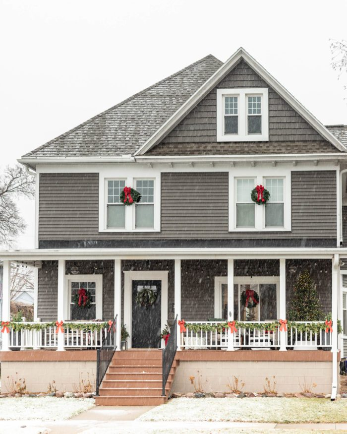Dark Gray house with Christmas Wreaths on windows.