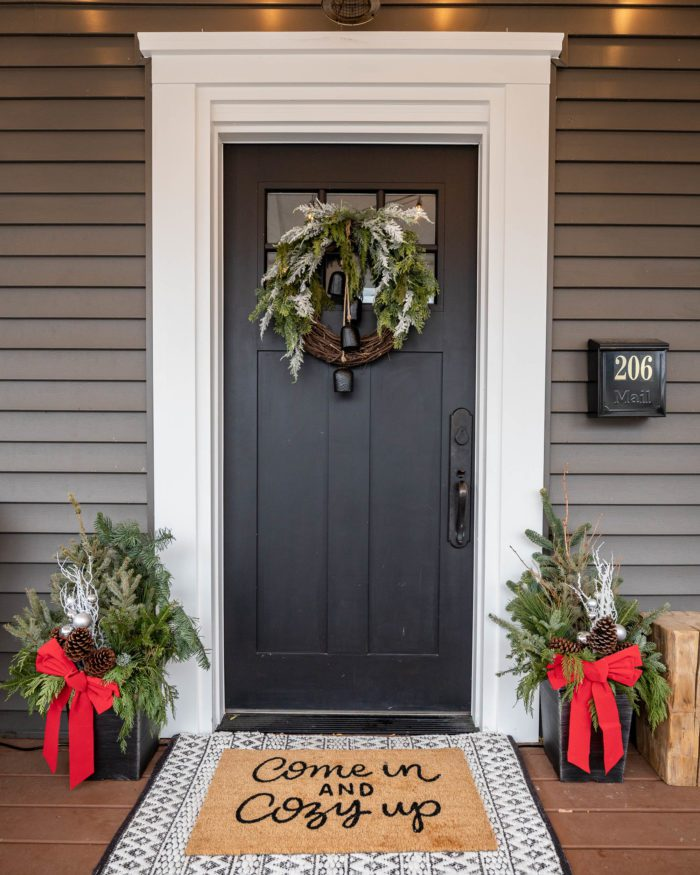 Black front door with Christmas wreath and decor.
