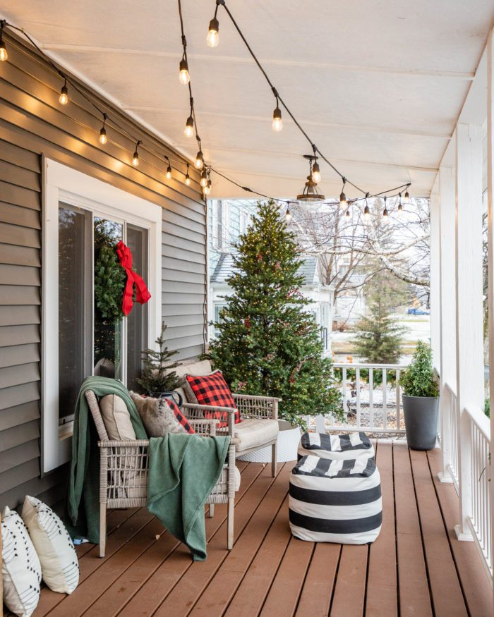 Classic Christmas Porch Decor with cozy pillows, poufs, and overhead cafe lighting.