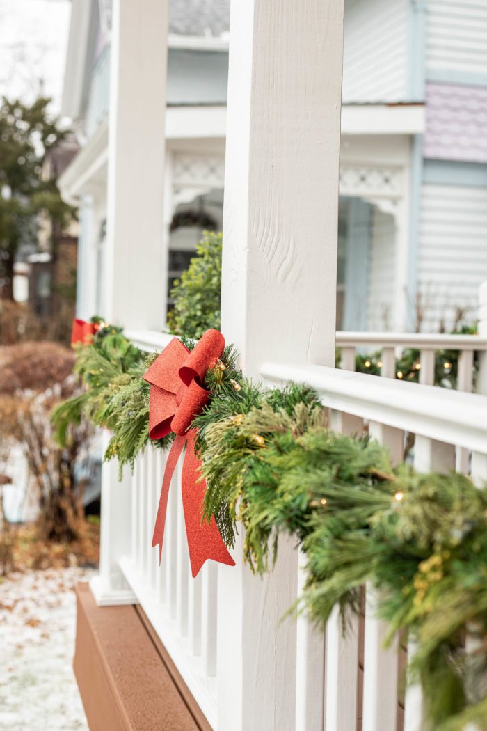 Classic Christmas Porch Decor, Garland with Red Bows on Porch Railing.