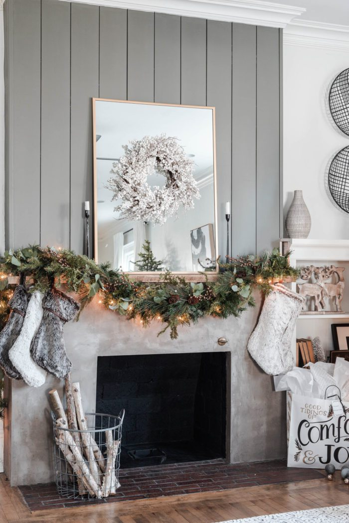 concrete fireplace with shiplap decorated for Christmas.