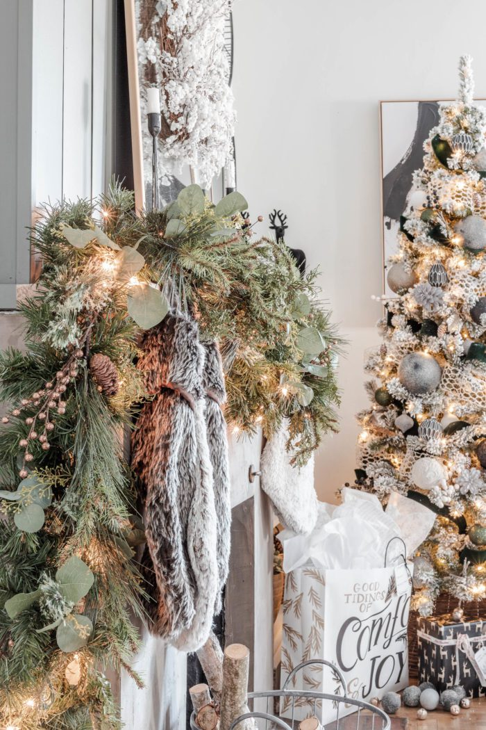 Faux garland mixed with stems and fresh clippings to create decor for a Rustic Luxe Christmas Mantel.