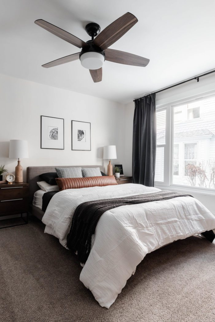 How to Make Your Bed like a Designer - The Streamlined looks featuring clean lines. Queen size bed with a modern gray headboard, white bedding, dark gray accents and a leather lumbar pillow.